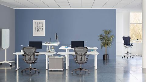 A collaboration area featuring white height-adjustable Atlas Office Landscape desks and black Aeron office chairs.