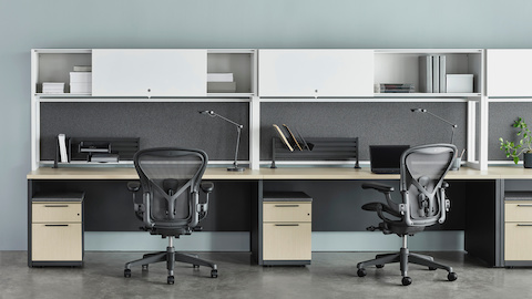 Canvas Metal Desk with white upper storage, grey tackboards, and grey Aeron Chairs. Select to go to the Canvas Metal Desk product page.