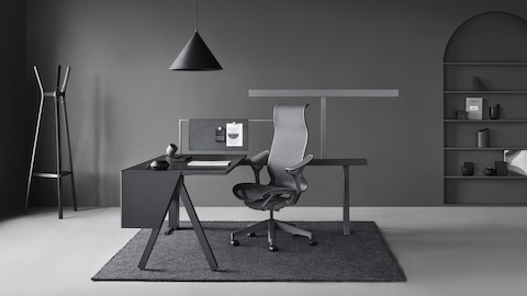 A Canvas Vista workstation in black and gray with a dark gray Cosm office chair. Select to go to the Canvas Vista product page.