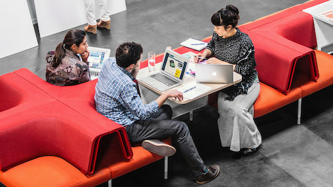 Man and two women collaborating in arrangement of red Public Office Landscape seating
