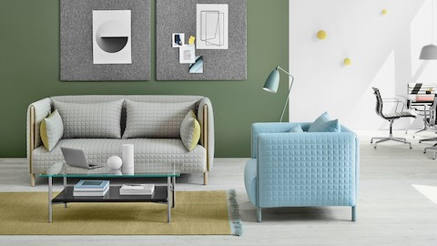 A light gray ColourForm loveseat and a light blue ColourForm lounge chair in a casual interaction space.