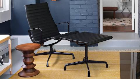 Eames Aluminum Group Lounge Chair and Ottoman with eggplant frames and black leather next to an Eames Walnut Stool. Select to go to the Eames Aluminum Group product page.