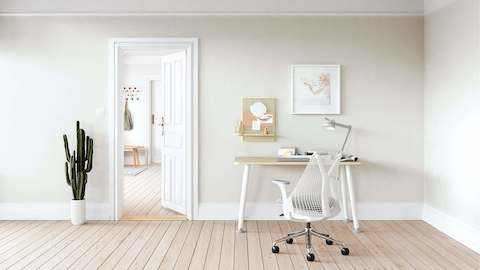 A white Sayl Chair at a Memo Desk in a bright home office.