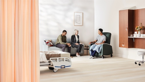 A patient sitting in a dark green Sahara recliner talks with a family member and physician sitting on a light gray Pamona Flop Sofa in a patient room with a patient bed nearby.