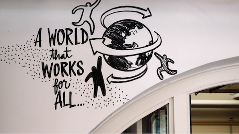 An illustration along a wall of three people and the world