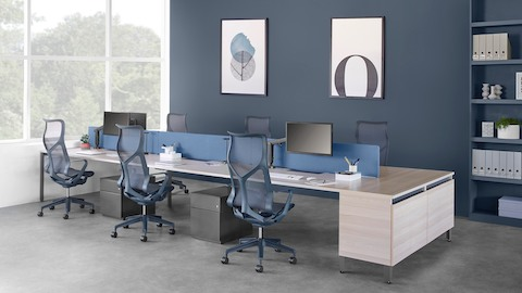 Six-person Layout Studio bench with a blue divider screen and attached credenza, dark blue Cosm chairs and under desk storage.