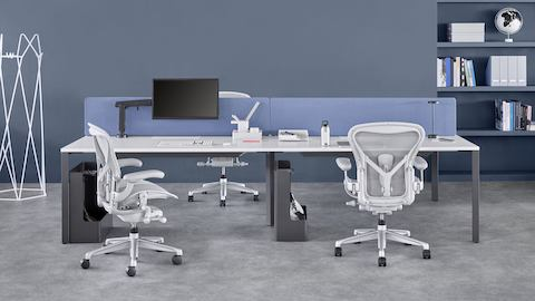 Four-person Layout Studio bench with a blue divider screen and light gray Aeron chairs. Select to go to the Layout Studio product page.