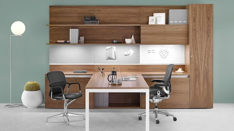 Layout Workwall and attached desk with a black Taper chair and Keyn side chair. Select to go to the Layout Workwall product page.