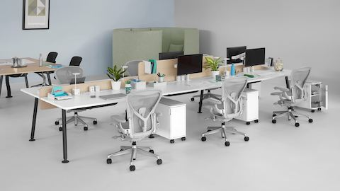 An open work area featuring a Memo meeting table and six Memo benching surfaces with light grey Aeron office chairs. Select to go to the Memo product page.