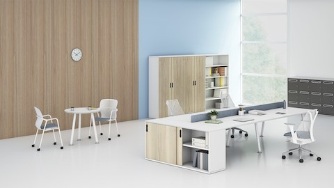 Clubhouse setting showing a Memo bench and Sayl chairs next to a white Memo round table. Select to go to the Memo product page.