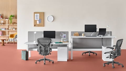 Nevi Link standing desk system with rectangular work surfaces with one of the four desks at a raised standing height. Select to go to the Nevi Link product page.