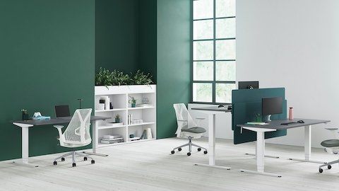 Three grey and white Nevi Sit-Stand Desks and Sayl Chairs in an informal office setting.