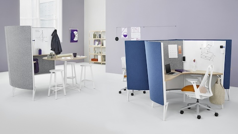 A Prospect collaborative space near two Prospect solo spaces with blue acoustic fabric and white Sayl Chairs. Select to go to the Prospect product page.