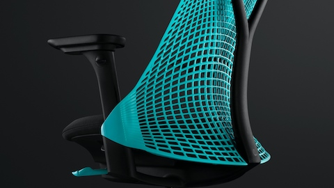 An Ocean Deep blue Sayl Chair, shown at an angle, on a black background.