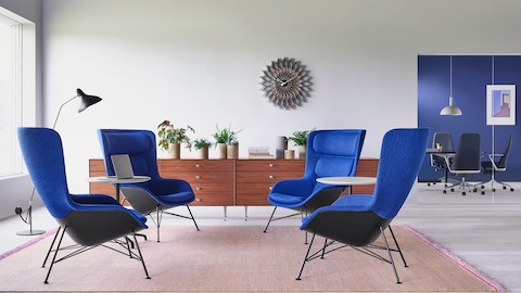 A Casual Setting Featuring Four Blue Striad Lounge Chairs With Two Tables Between Them