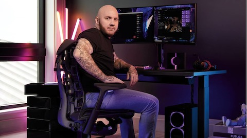 A man wearing headphones sits in the Gaming Chair, facing a set-up with a gaming keyboard, mouse and dual monitors.