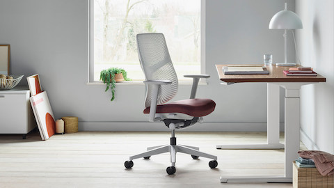 A white Verus Chair with dark red seat next to a Renew Sit-to-Stand Table with a wood surface close to a window. Select to go to the Verus Chairs product page.