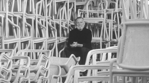 Designer Ward Bennett sits among dozens of stacked chairs.