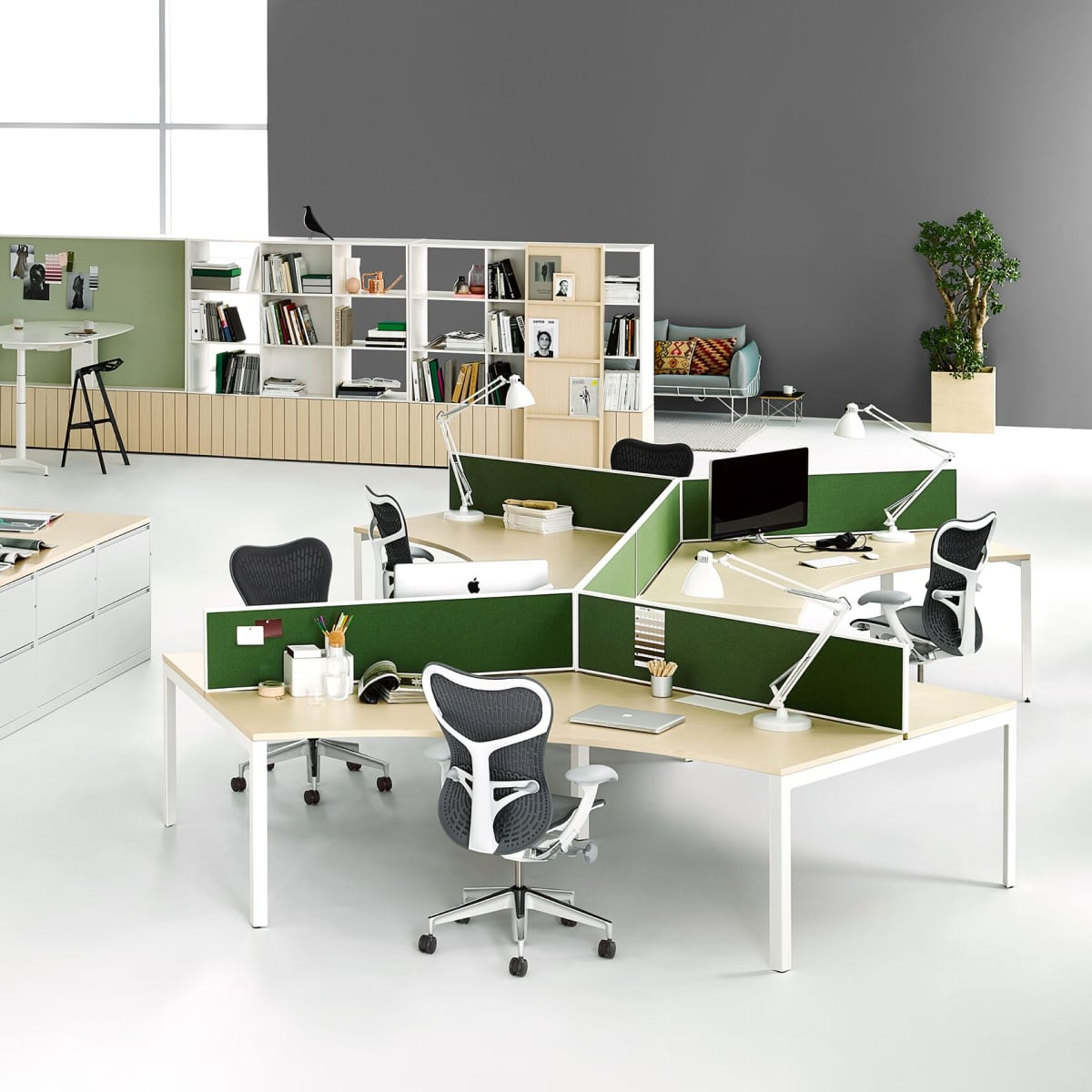 Workstations with green privacy screens and dark blue Mirra 2 office chairs.