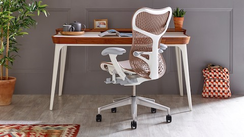 A Mirra 2 ergonomic desk chair with tan back and white frame at an Airia desk with white legs and walnut trim. Select to go to the Mirra 2 product page.