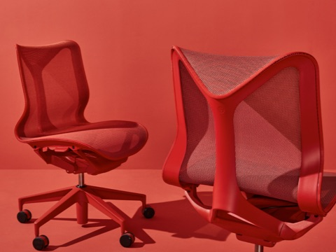 Two armless low-back Cosm Chairs in Canyon red on a red background.