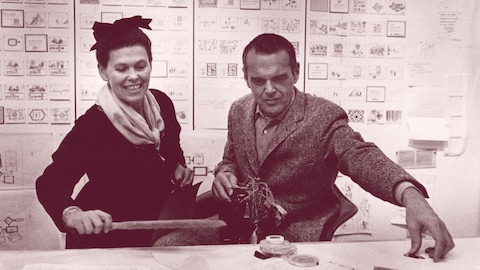 Designers Charles and Ray Eames working side by side placing and arranging objects on the table. Select to learn about their thoughts on design.