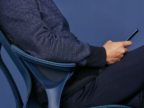 A man wearing a navy blue sweater sits in a Nightfall navy blue Cosm chair with leaf arms.