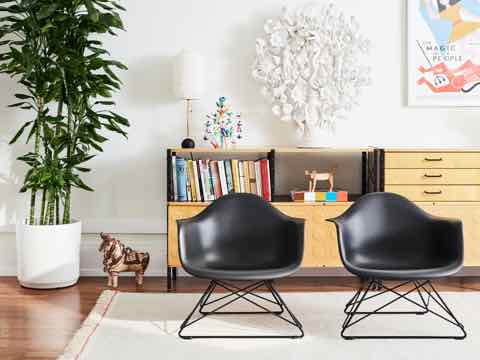 A living space with a pair of black Eames Shell Chairs with Low Wire Bases in the foreground, and a plant, a variety of books and decorative objects, and an Eames Storage Unit behind. Select to go to the Eames Shell Chair family page.