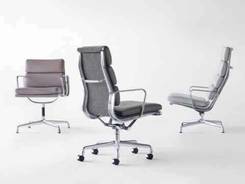 A group of Eames Soft Pad Chairs, including Side Chairs and Lounge Chairs on four-star bases with glides and an Executive Chair on a five-start base with casters, showcases curated parings of Hallingdal textiles in gray heather on the back with coordinating MCL Leather on the seat and back cushions.
