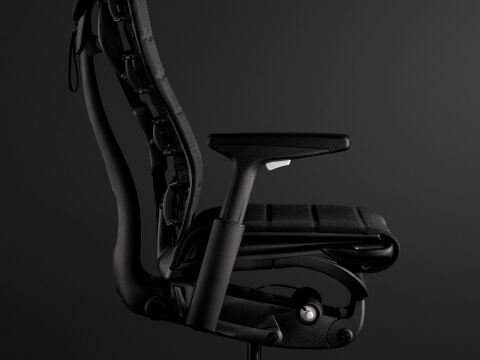 The new black and white Embody Gaming Chair from the side, showcasing its back, seat, and arms.