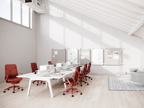 Six red Cosm chairs around an Optimis Desking System in a work area with Exclave.