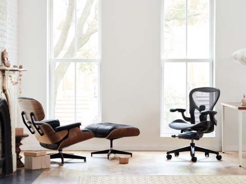 Brightly lit room with Eames Lounge Chair and Ottoman in black leather, viewed from the side and Aeron Chair in graphite, viewed from a front angle.