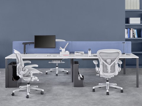 Four-person Layout Studio bench with a blue divider screen, three light grey Aeron chairs and under-desk storage.