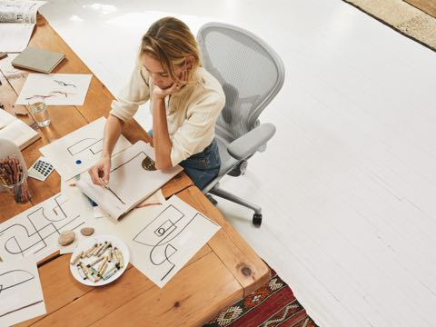 A woman sitting at a desk in her Aeron Chair, sketching shapes and designs on paper.