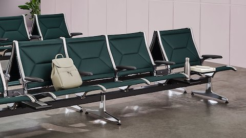 Rows of Eames Tandem Sling Seating with black leather upholstery and aluminum frames. Select to go to the Eames Tandem Sling Seating product page.