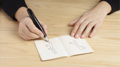A person wearing a black shirt uses a pen to sketch out parts of the Mattiazzi Branca Chair in a notebook that rests on a light wood table. Select to read the WHY story about Industrial Facility.