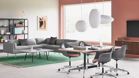 A brightly lit work environment featuring Eames Task Chairs around a meeting table in the foreground. Bolster Sofas and Steelwood Shelving on a green rug provide a lounge setting in the space.