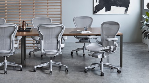 Light gray Aeron office chairs on both sides of a rectangular conference table. Select to go to the Aeron product page.