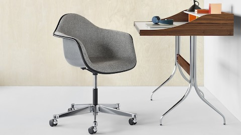 A gray Eames Molded Fiberglass Chair seated in front of a Nelson Swag Leg Desk in an individual workstation setting.