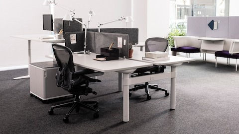 An open office with Atlas Office Landscape workstations and black Aeron Chairs. Select to go to the Atlas Office Landscape product page.