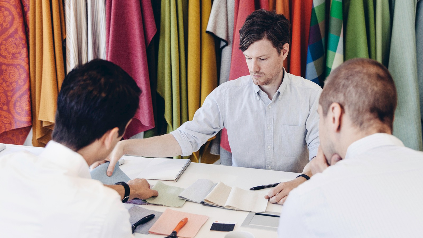 Four seated men review fabric samples.
