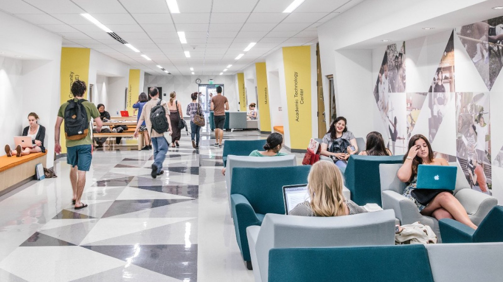 A well-lit hallway with students studying in Swoop Lounge Furniture. Select to find out how we help college and university leaders create learning spaces that can keep pace with students.