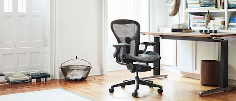 Aeron Chair in Graphite seen at an angle in front of a Renew Sit-to-Stand Desk in a bright room.