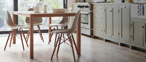Kitchen seen in natural light featuring the Doubleframe Table in oak with four plastic Shell Chairs in stone with a dowel base.