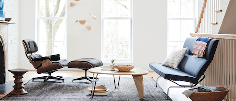 An Eames Compact Sofa, Eames Lounge Chair and Ottoman, and Noguchi Rudder Table seen in a brightly lit room.