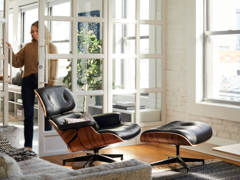 Eames Lounge Chair and Ottoman in a sunny living room with a sofa and coffee table off to the side.