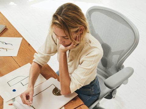 A woman sketching designs while sitting in the Aeron Chair.