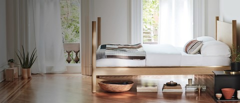 The Pillar Bed in oak is seen from the side in warm light.