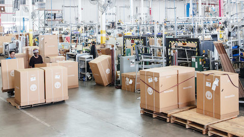 A view across an open factory floor where Herman Miller furniture is being packaged in boxes on pallets.