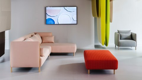 Three ColourForm seating pieces, a pink sectional, red ottoman, and gray lounge chair, beneath hanging textiles in shades of green.